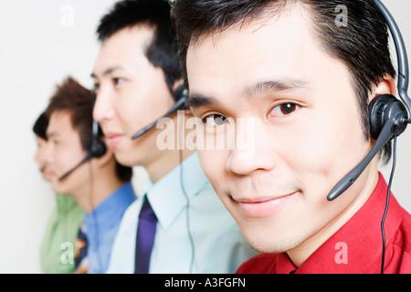 Vier Vertreter reden über Kopfhörer - Stockfoto