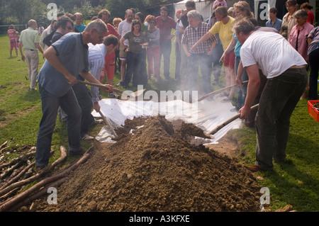 Abdecken der Grube Ofen bei einem Curanto, Kochen in einer Grube Ofen, Gemüse und Fleisch kochen auf heißen Steinen - Stockfoto