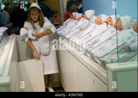 Ein Verkäufer gekleidet wie eine Krankenschwester Neugeborenen Puppen auf die Mutterschaft in den Spielzeugladen - Stockfoto