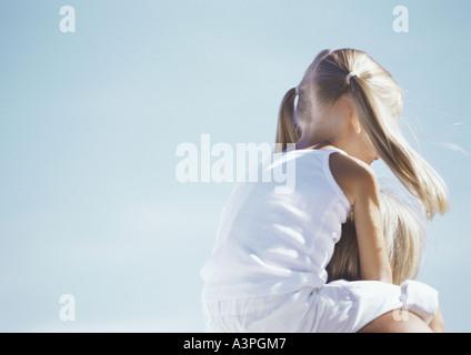 Kleines Mädchen reiten auf Mutters Schultern - Stockfoto