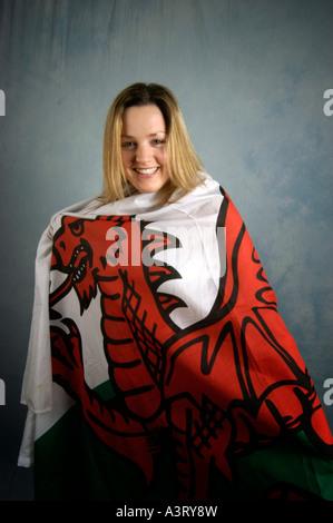 Junge lächelnde blonde Frau eingewickelt in walisische Nationalflagge - Stockfoto