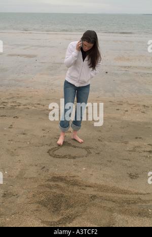 Langhaarige Teenager-Mädchen telefonieren mit ihrem Handy und zeichnen die Form eines Herzens mit ihrem Fuß auf - Stockfoto