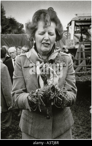 Frau Thatcher komischen Gesicht ziehen, wie sie Gülle auf einem Bauernhof abholt Stockfoto