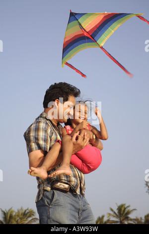 Vater und Tochter, die Spaß am Picknick Drachen am Strand und genießen Sie Sonne, Sand und Meer - Stockfoto