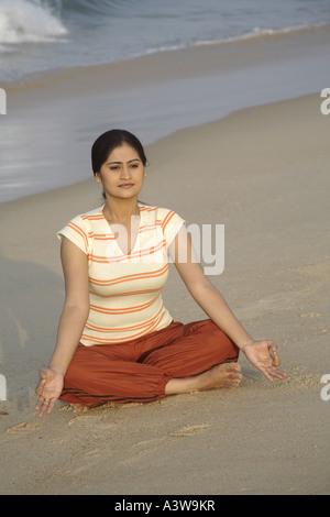 Frauen im Urlaub tun Yoga Übung sitzen am Strand und genießen Sie Sonne, Sand, Meer - Stockfoto