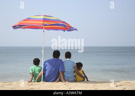 Vierköpfige Familie sitzen unter Sonnenschirm am Strand mit Blick auf das Meer - Stockfoto