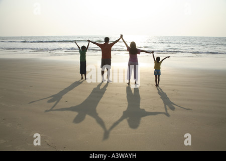 Familie von vier spielen mit Schatten am Strand - Stockfoto