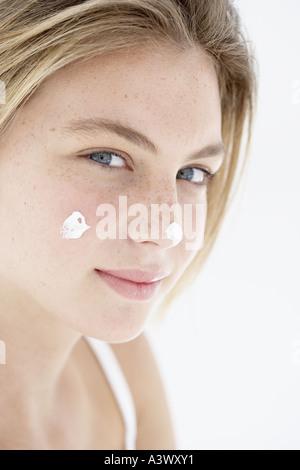 Eine junge Frau, die Anwendung der Creme im Gesicht - Stockfoto