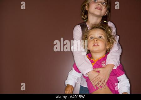 Mädchen hält erstaunt aussehende kleine Schwester - Stockfoto