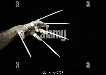 Die Hand des Mannes mit Stäbchen gebunden an Fingern - Stockfoto