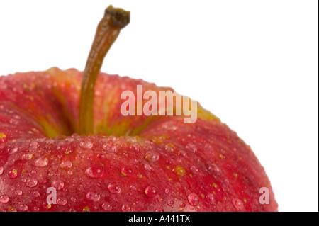 Roter Apfel mit Wassertropfen auf isoliert auf weißen geringe Schärfentiefe gerahmt in der linken Ecke, um Raum - Stockfoto