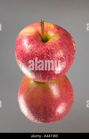 Roter Apfel in Tröpfchen reflektiert Spiegelkarte abgedeckt - Stockfoto