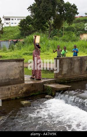 Menschen vor Ort füllen Eimer mit Wasser zum trinken, Luba Stadt, SW der Insel Bioko, Äquatorialguinea, Zentralafrika - Stockfoto
