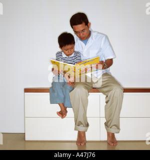 Vater mit Sohn lesen - Stockfoto