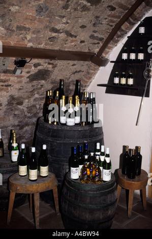 Bratislava, Slowakei: Flaschen Wein auf Fässer im Keller eines slowakischen Weinbergs angezeigt. - Stockfoto