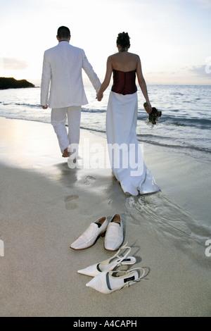 Braut und Bräutigam zu Fuß am Strand mit ihren Schuhen im Vordergrund - Stockfoto
