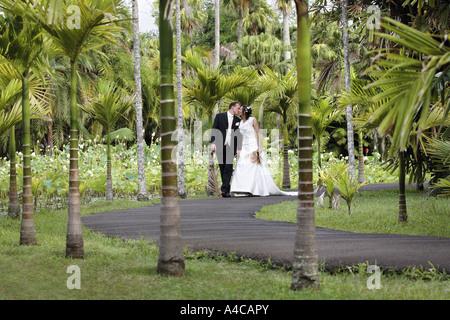 Braut und Bräutigam zu Fuß in einem tropischen Garten - Stockfoto