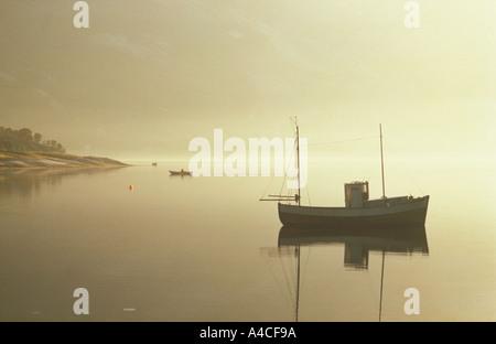 Kleines Fischerboot verankert im norwegischen Fjord mit Mann im Ruderboot - Stockfoto