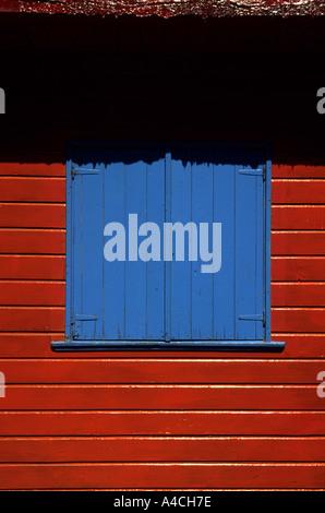 Buenos Aires, Argentinien. Bunt bemalten blauen Fensterläden in einer roten Wand im Stadtteil La Boca. - Stockfoto