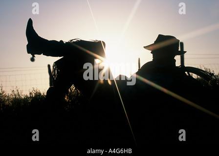 Silhouette eines Cowboys in den Rasen mit seinem Bein auflegen - Stockfoto
