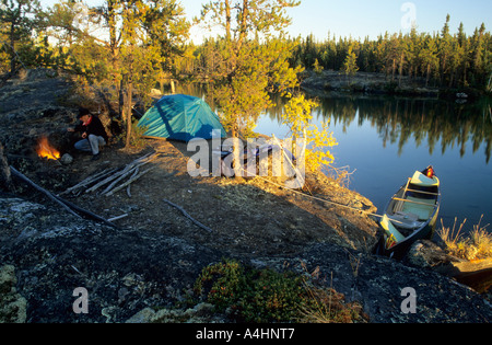 Mann am Lagerfeuer an einem Seeufer, Nordwest-Territorien, Kanada - Stockfoto