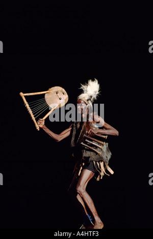 Ein afrikanischer Musiker und Tänzer aus Côte d ' Ivoire (Elfenbeinküste) in Westafrika auf der Bühne in traditioneller - Stockfoto