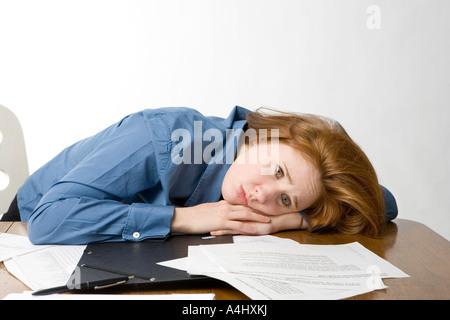 Traurig Geschäftsfrau, die ihren Kopf auf ihrem Schreibtisch ruhen - Stockfoto