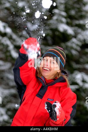Frau in Outdoor-Bekleidung, Schneeball werfen - Stockfoto