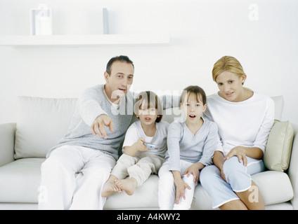 Eltern mit auf Sofa sitzend mit Tochter und Sohn, Vater zeigt geradeaus - Stockfoto