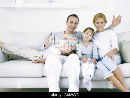 Eltern mit auf Sofa sitzend mit Tochter und Sohn, Blick in die Kamera - Stockfoto