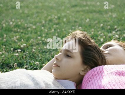 Mädchen und Mutter liegen auf dem Rasen - Stockfoto