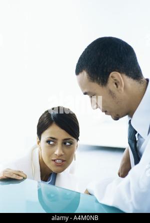 Geschäftsfrau sucht aus den Ecken der Augen, im Gespräch mit Geschäftsmann - Stockfoto