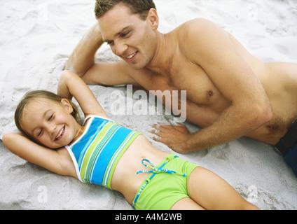 Mädchen und Vater am Strand liegen - Stockfoto