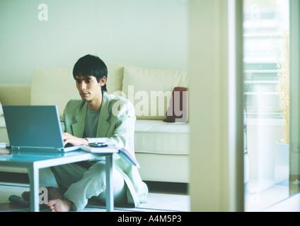 Junger Mann am Boden, mit Laptop auf Couchtisch - Stockfoto