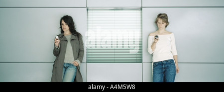 Zwei junge Frauen Wand gelehnt, Blick auf Handys - Stockfoto