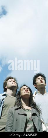 Junge Menschen stehen zusammen, Sonne Shinging auf ihren Gesichtern, Augen geschlossen, niedrigen Winkel Ansicht - Stockfoto