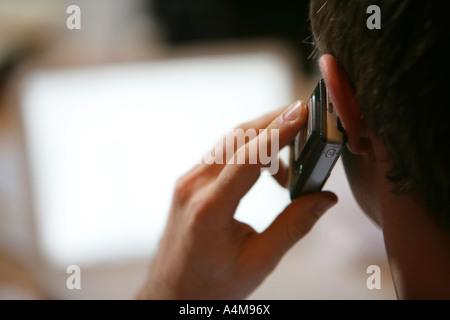 DEU-Deutschland-Mann mit einem Mobiltelefon in einem Büro - Stockfoto