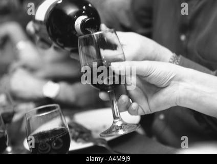 Man gießt Wein für Frau - Stockfoto