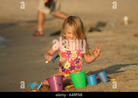 Kleine Mädchen spielen im Sand am Strand - Stockfoto