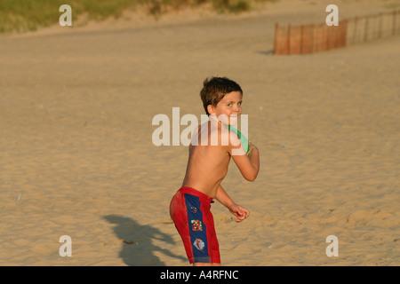 Junge Junge werfen Frisbee am Strand - Stockfoto