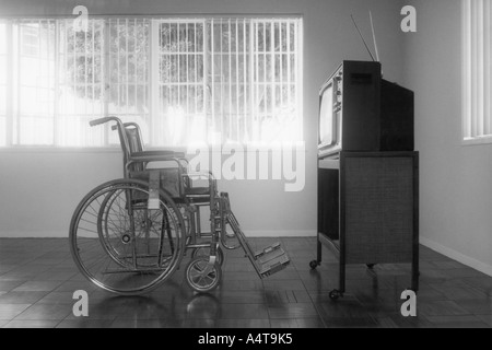 Leeren Rollstuhl sitzt vor einem leeren Fernseher einstellen - Stockfoto
