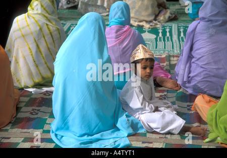 Frauen und ein Kind sitzt in der Moschee während der Eid el Fitr Gebete, Ajmer, Indien - Stockfoto