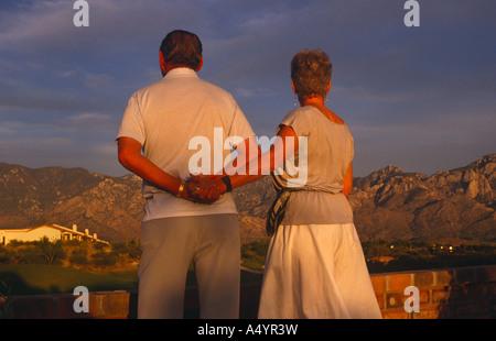 Ältere Ehepaar an den Händen halten und beobachten Sie den Sonnenuntergang in ihrem Haus in Tucson, Arizona. USA - Stockfoto