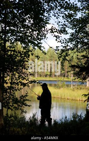 Silhouette von einem älteren Fischer angeln in einem kleinen Waldsee, Finnland - Stockfoto