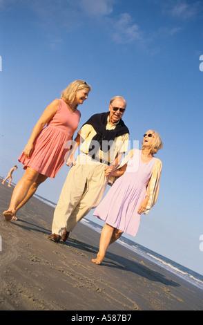 Älteres Ehepaar und ihre erwachsene Tochter, die Hand in Hand bei einem Spaziergang am Strand entlang - Stockfoto
