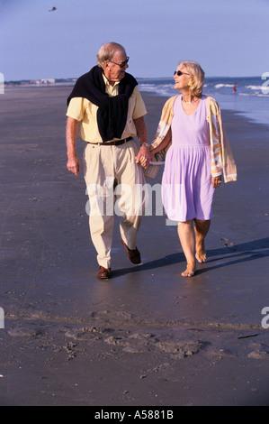Älteres Paar Hand in Hand und spazieren am Strand entlang während Sie den Blick in jedes andere Augen - Stockfoto