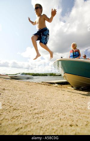 Kinder springen von einem Boot auf einem Strand - Stockfoto