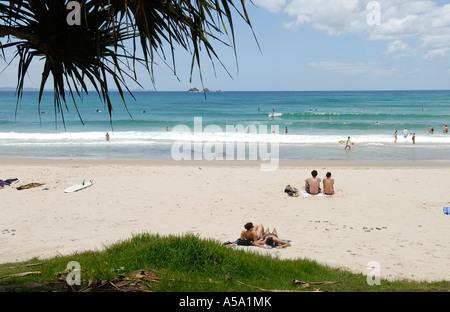 Sonnenanbeter beobachten die Brandung an einem weißen Sandstrand. St. Julian-Insel in der Ferne. - Stockfoto