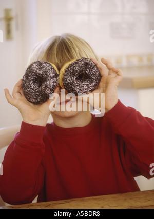 Kleiner Junge mit einem Donut-Ring, die Spaß an einem Küchentisch sitzen - Stockfoto