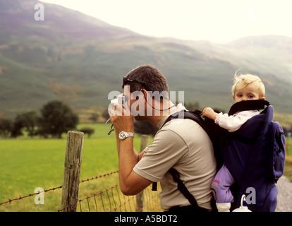 Vater im Urlaub am Buttermere im Lake District in Großbritannien fotografieren mit seiner Tochter in einem Rucksack - Stockfoto